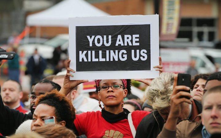 """Irkçılık karşıtı protestolarda elinde """"Bizi öldürüyorsunuz"""" pankartı taşıyan protestocu."""